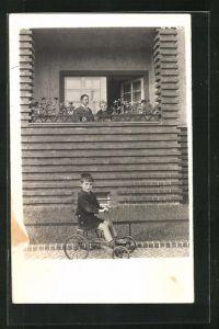 Foto-AK Kleiner Junge mit Dreirad vor einem Fenster