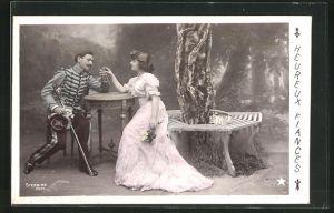 Foto-AK Stebbing: La Bague de Fiancailles, Herr in Uniform und Dame sitzen am Tisch unter einem Baum