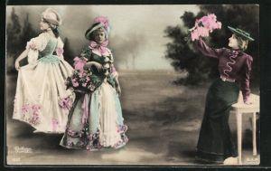 Foto-AK Atelier Reutlinger, Paris: Frauen in aufwändigen Kleidern mit Blumen