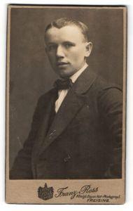 Fotografie Franz Ress, Freising, Portrait junger Herr mit zeitgenöss. Frisur u. Fliege im Anzug