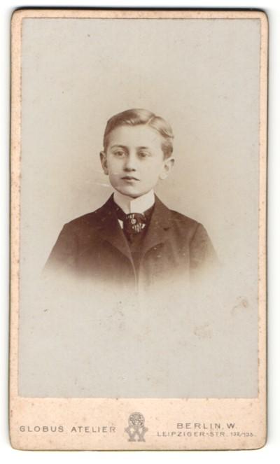 Fotografie Atelier Globus, Berlin W., Portrait kleiner Junge mit Seitenscheitel u. Krawatte im Anzug