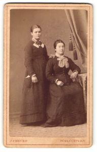 Fotografie J. Freund, Schlüchtern, Portrait bürgerliche Dame mit zurückgebundenem Haar am Tisch sitzend u. andere Dame