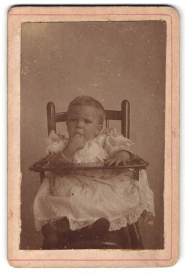 Fotografie Fotograf unbekannt, Ort unbekannt, kleines Mädchen in Spitzenkleid im Hochstuhl sitzend