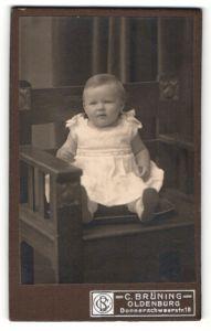 Fotografie C. Brüning, Oldenburg, Portrait niedliches Kleinkind im weissen Kleid auf Stuhl sitzend