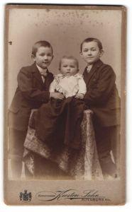 Fotografie Kersten Sohn, Altenburg s / A., Portrait zwei kleine Jungen in Anzügen u. kleine Schwester auf Tisch sitzend