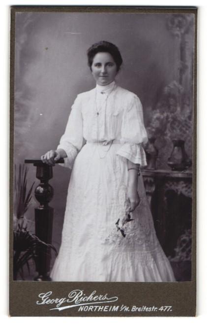 Fotografie Georg Richers, Northeim, elegante Dame in Spitzenkleid mit langer Kette und Blumen in der Hand