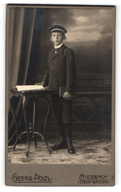 Fotografie Georg Pöltl, Miesbach, Junge in Anzug mit Mütze und kurzen Hosen mit Buch in der Hand