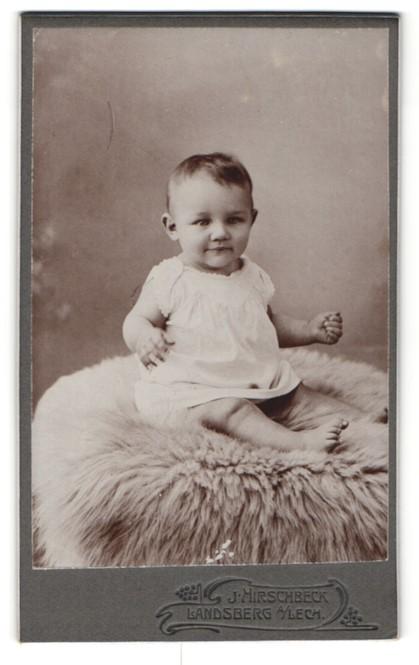 Fotografie J. Hirschbeck, Landsberg, Baby in Hemdchen mit nackten Beinen auf Pelz