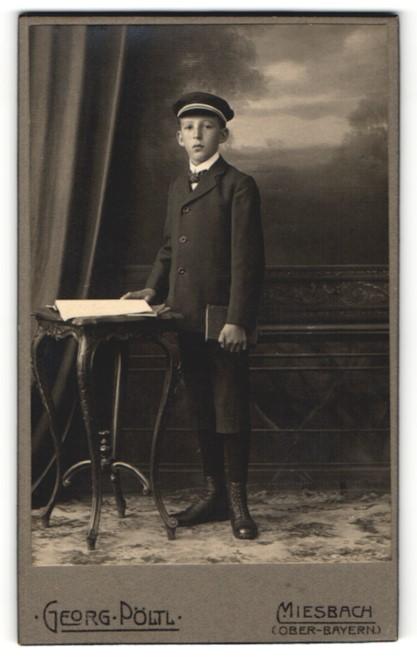 Fotografie Georg Pöltl, Miesbach, Junge in Anzug mit kurzen Hosen mit Mütze und Buch haltend