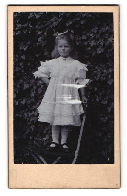 Fotografie Fotograf unbekannt, Ort unbekannt, kleines Mädchen in Rüschenkleid mit Schleife im Haar