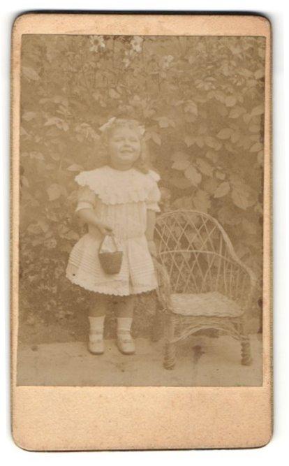 Fotografie Fotograf unbekannt, Ort unbekannt, kleines Mädchen in Rüschenkleid mit Eimerchen und lachend