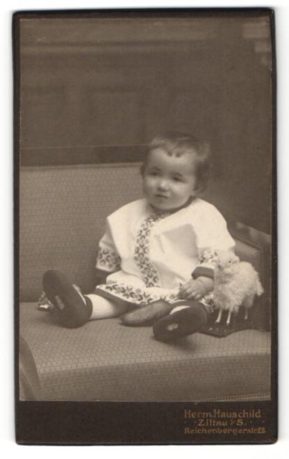 Fotografie Herm. Hauschild, Zittau, kleines Mädchen in besticktem Kleid mit Schaf Spielzeug 0