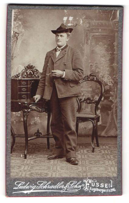 Fotografie Ludwig Schradler & Sohn, Füssen, Mann in Jägermontur mit Zigarillo