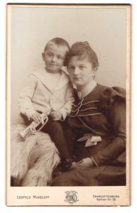 Fotografie Leopold Minzloff, Berlin-Charlottenburg, Portrait schöne junge Mutter und frech grinsender Bube mit Trompete