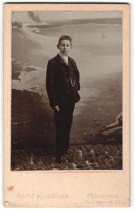 Fotografie Adolf Koestler, München, Portrait dunkelhaariger Knabe im eleganten Anzug vor einer Gebirgsleinwand