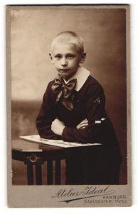 Fotografie Atelier Ideal, Hamburg, Portrait frecher blonder Bube mit grosser Schleife am Kragen