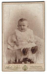 Fotografie Atelier Victoria, Frankfurt / Oder, Baby im Taufkleid auf Felldecke sitzend