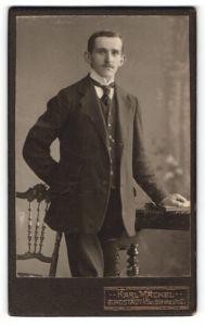 Fotografie Karl Mäckel, Burgstädt i / Sa., Portrait charmanter Herr mit Buch im Anzug an Tisch gelehnt