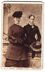 Fotografie Geo. C. Caster, Peterborough, elegante Dame mit Hut, Handschuhen und Schrim u. junge sehr schlanker Frau