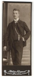 Fotografie Atelier Elegant, Berlin, Portrait junger Herr mit Oberlippenbart u. Krawatte im Anzug an Stuhl gelehnt