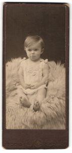 Fotografie J. Fuchs, Schöneberg, Portrait niedliches Kleinkind im weissen Hemd auf Fell sitzend