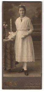 Fotografie William Roth, Berlin S. O., Portrait junge Dame im weissen Kleid mit Buch u. Kerze an Tisch glehnt