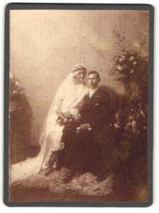 Fotografie unbekannter Fotograf und Ort, Portrait bürgerliches Paar mit Blumen in hübscher Hochzeitskleidung