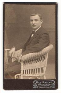 Fotografie Rich. Radtke, Sömmerda, Portrait charmanter Herr mit Fliege im Anzug im Korbstuhl sitzend