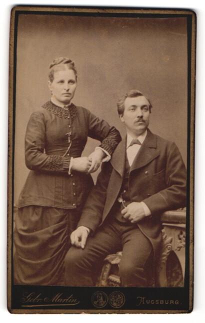 Fotografie Gebr. Martin, Augsburg, Portrait bürgerlicher Herr im Anzug auf Hocker sitzend und Dame in zeitgenöss. Kleid