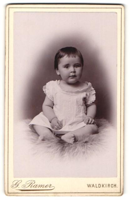 Fotografie G. Ramer, Waldkirch, Portrait niedliches Kleinkind im weissen Kleid auf Fell sitzend