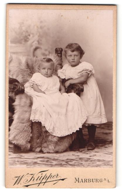 Fotografie W. Küpper, Marburg a / L., Portrait niedliches Kleinkind im weissen Kleid auf Fell sitzend u. Schwester