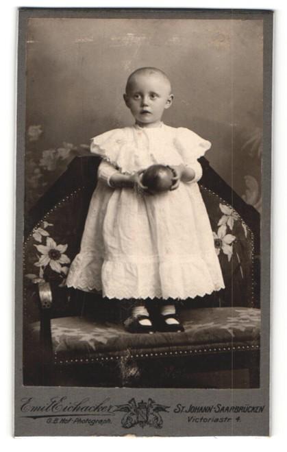 Fotografie Emil Eichacker, St. Johann-Saarbrücken, Portrait niedliches Kleinkind mit Ball auf Bank stehend