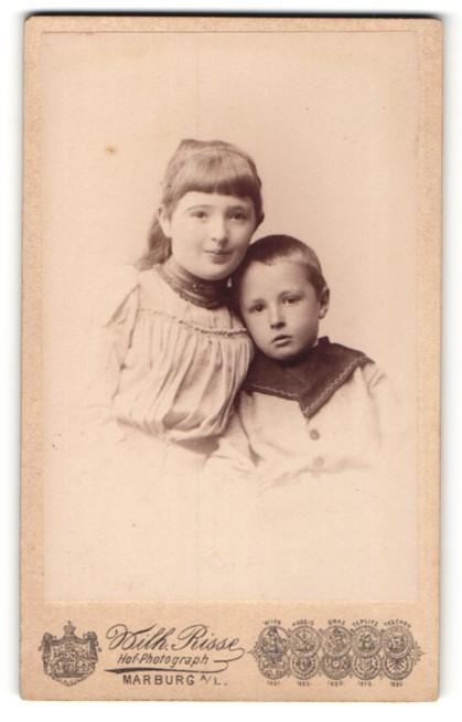 Fotografie Wilh. Risse, Marburg a / L., Portrait kleines Mädchen mit Ponyfrisur im hübschen Kleid u. Brüderchen