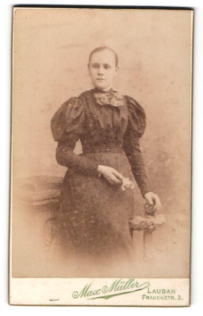 Fotografie Max Müller, Lauban, Portrait junge Dame mit zurückgebundenem Haar und Blume auf Knauf gestützt