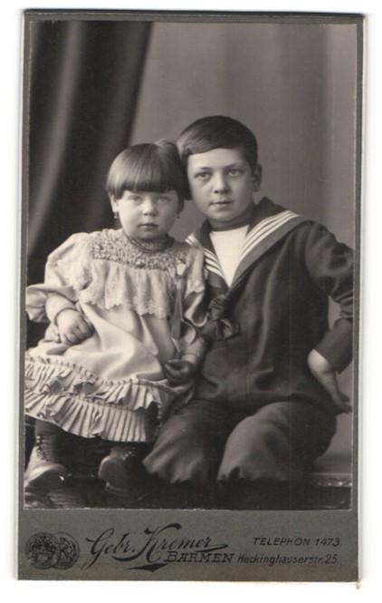 Fotografie Gebr. Kremer, Barmen, Portrait kleiner Junge im Matrosenanzug und Schwesterchen auf Bank sitzend