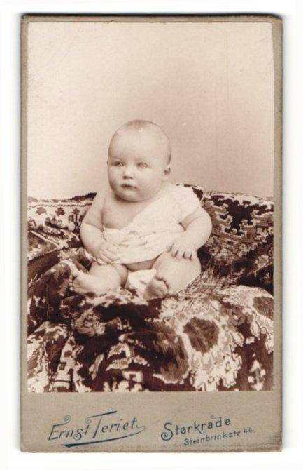 Fotografie Ernst Teriet, Sterkrade, Portrait niedliches Baby im weissen Hemd auf Sessel sitzend