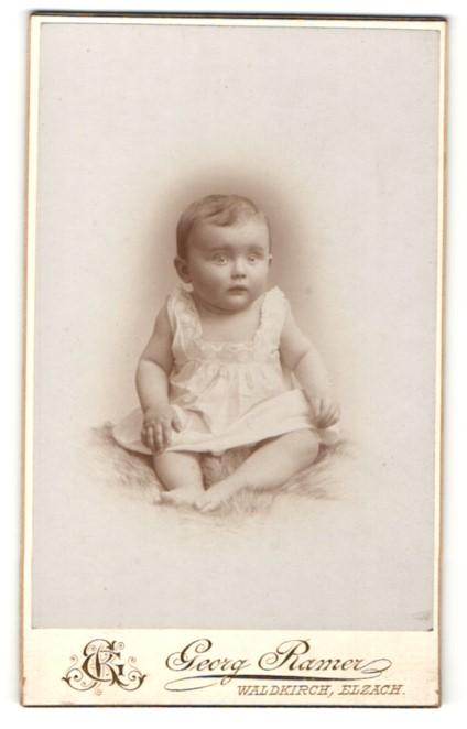 Fotografie Georg Ramer, Waldkirch, Portrait niedliches Baby im weissen Kleid auf Fell sitzend