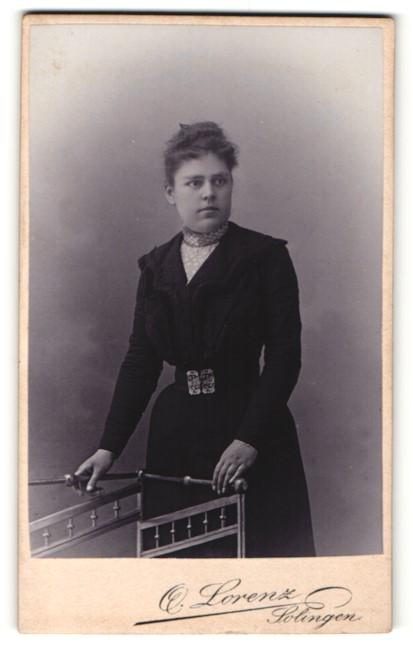 Fotografie Otto Lorenz, Solingen, Portrait junge Dame mit zeitgenöss. Frisur im eleganten Kleid an Geländer gelehnt