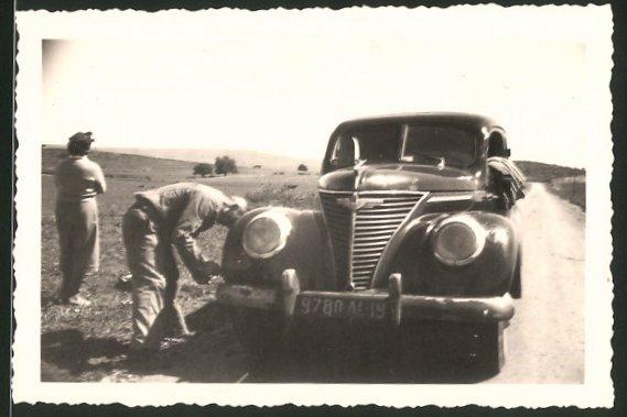 Fotografie Auto Ford, Fahrer tauscht das Vorderrad nach einer Reifenpanne