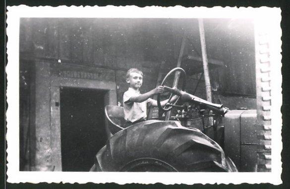 Fotografie Traktor, Knabe steuert Schlepper