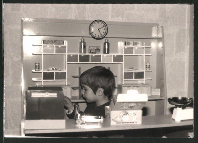 Fotografie Knabe spielt mit Kaufmannsladen