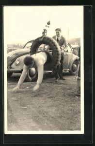 Foto-AK VW-Käfer, Mann springt durch einen Autoreifen
