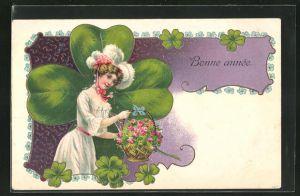 Präge-AK Dame mit einem Korb voller Rosen posiert vor einem Riesen-Glücksklee, Neujahr, Bonne Année