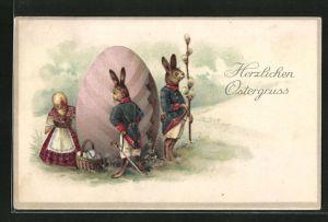AK Vermenschlichte Osterhasen und Osterküken bewachen ein grosses Osterei, Herzlichen Ostergruss
