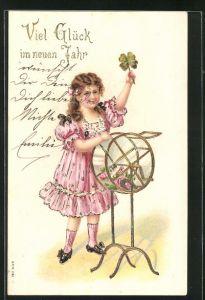 Präge-AK Mädchen mit Kleeblatt an einer Lostrommel, Neujahrsgruss
