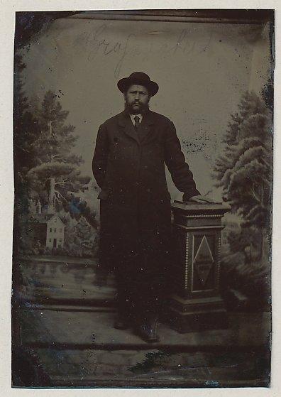 Fotografie Ferrotypie Edelmann mit Vollbart trägt Mantel und Hut, Säule mit Jahreszahl 1882