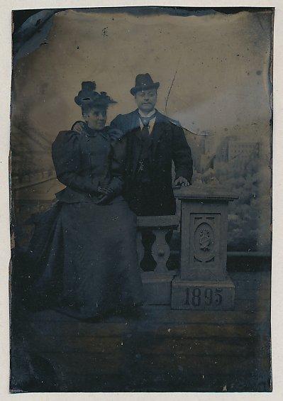 Fotografie Ferrotypie elegantes Paar im feinen Zwirn mit Hut, Säule mit Wappen und Jahreszahl 1895