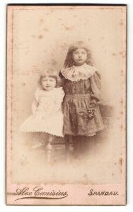 Fotografie Alex Canisius, Berlin, kleines Mädchen mit langen Haaren in gepunktetem Kleid mit kleinem Mädchen neben sich