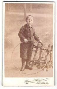 Fotografie Herm. Schlüter, Magdeburg, Portrait frecher blonder Bube mit Reifen