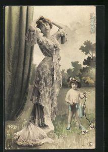 Foto-AK Atelier Reutlinger, Paris: Dame in besticktem Kleid mit Schleppe und Kind mit Pfeil und Bogen